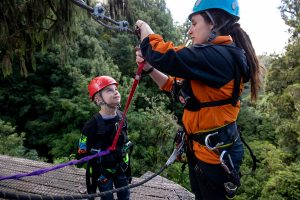 Canopy-tours-guide-attaching-child-to-zipline