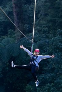 Woman-on-zipline-with-forest-behind