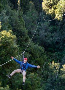 Man-smiling-on-zipline-through-forest