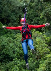 Woman-in-red-jacket-on-zipline-above-forest