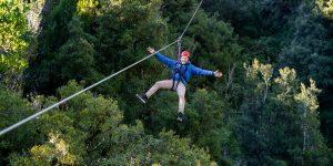 Man-smiling-on-zipline-above-forest