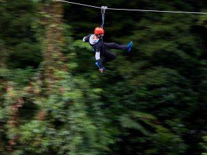 Man-speeding-through-forest-on-zipline