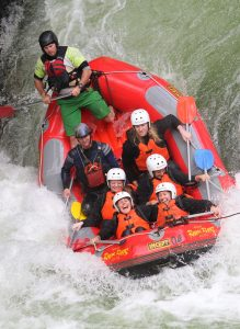 Group-of-people-in-raft-going-down-waterfall